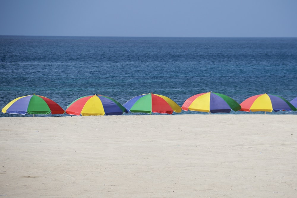 five parasols at the shore during day