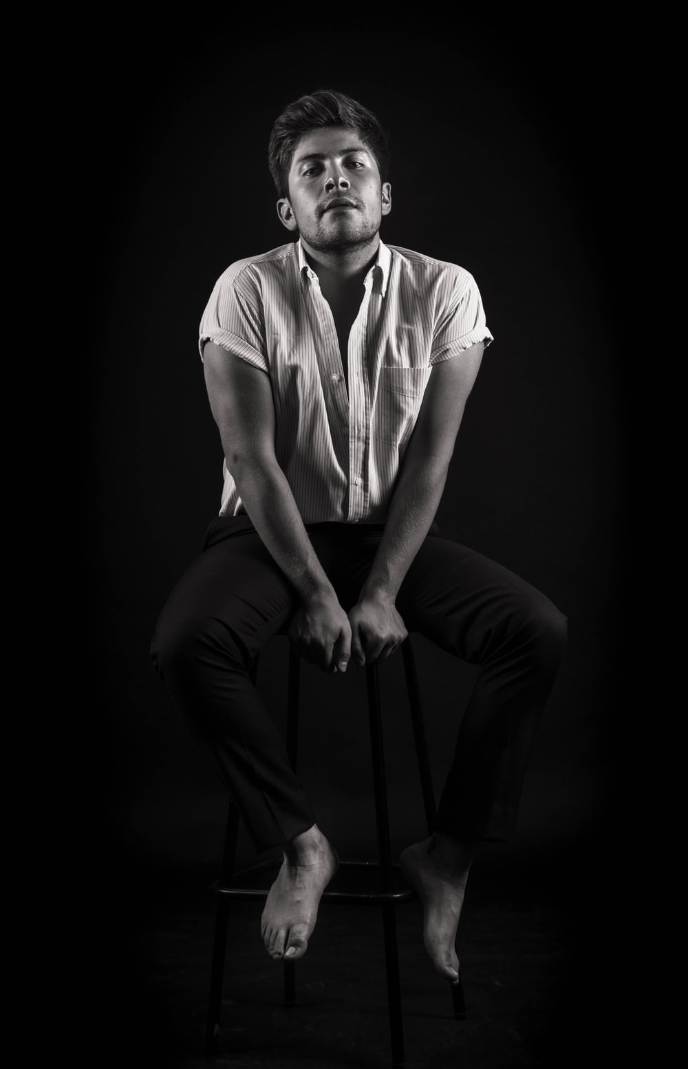 grayscale photography unknown person sitting on stool