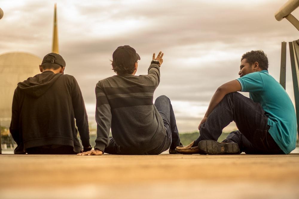 three men sitting on ground