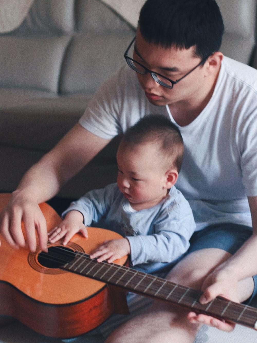 man wearing white crew-neck shirt beside baby holding guitar