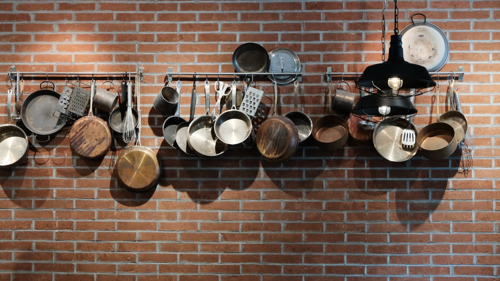 assorted cooking pan on wall rack
