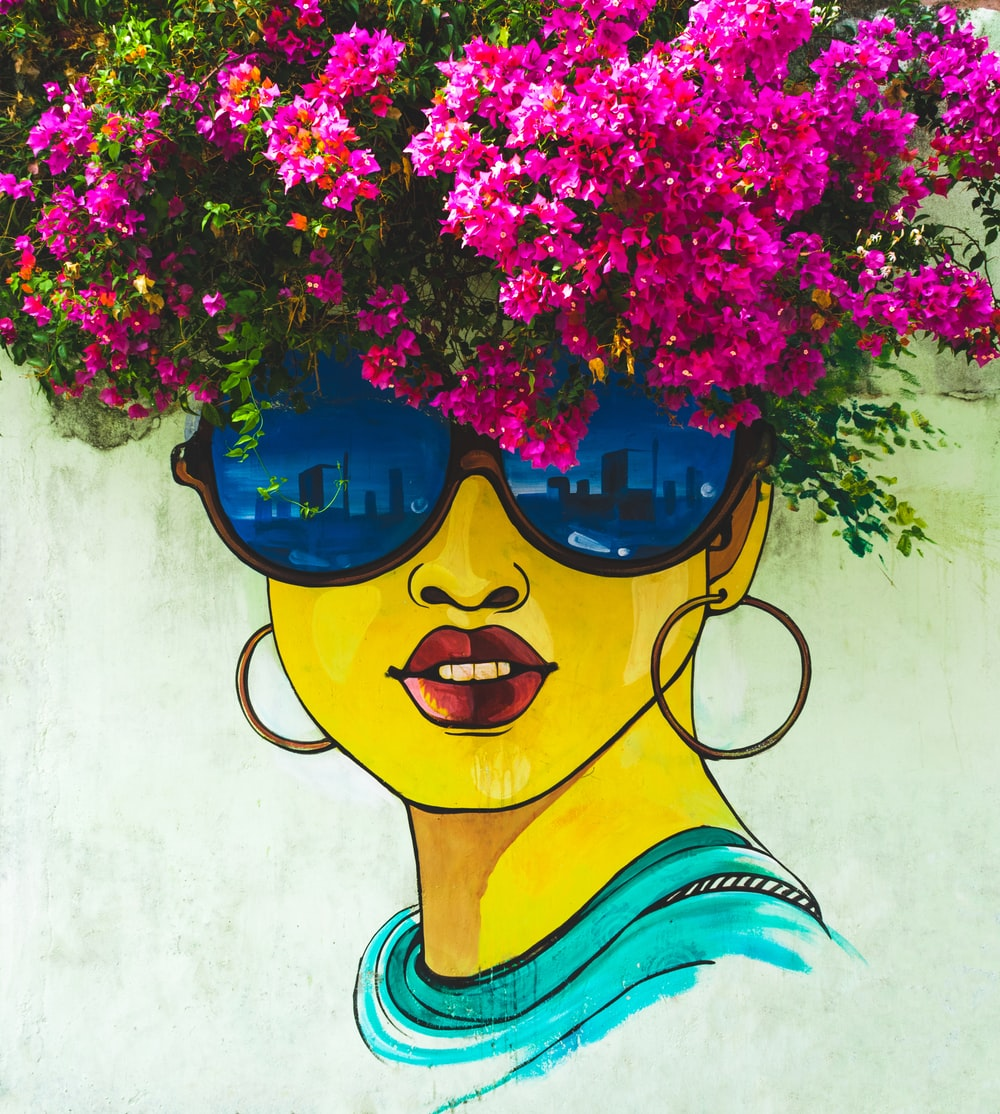 woman wearing sunglasses wall painting near pink bougainvillea flowers