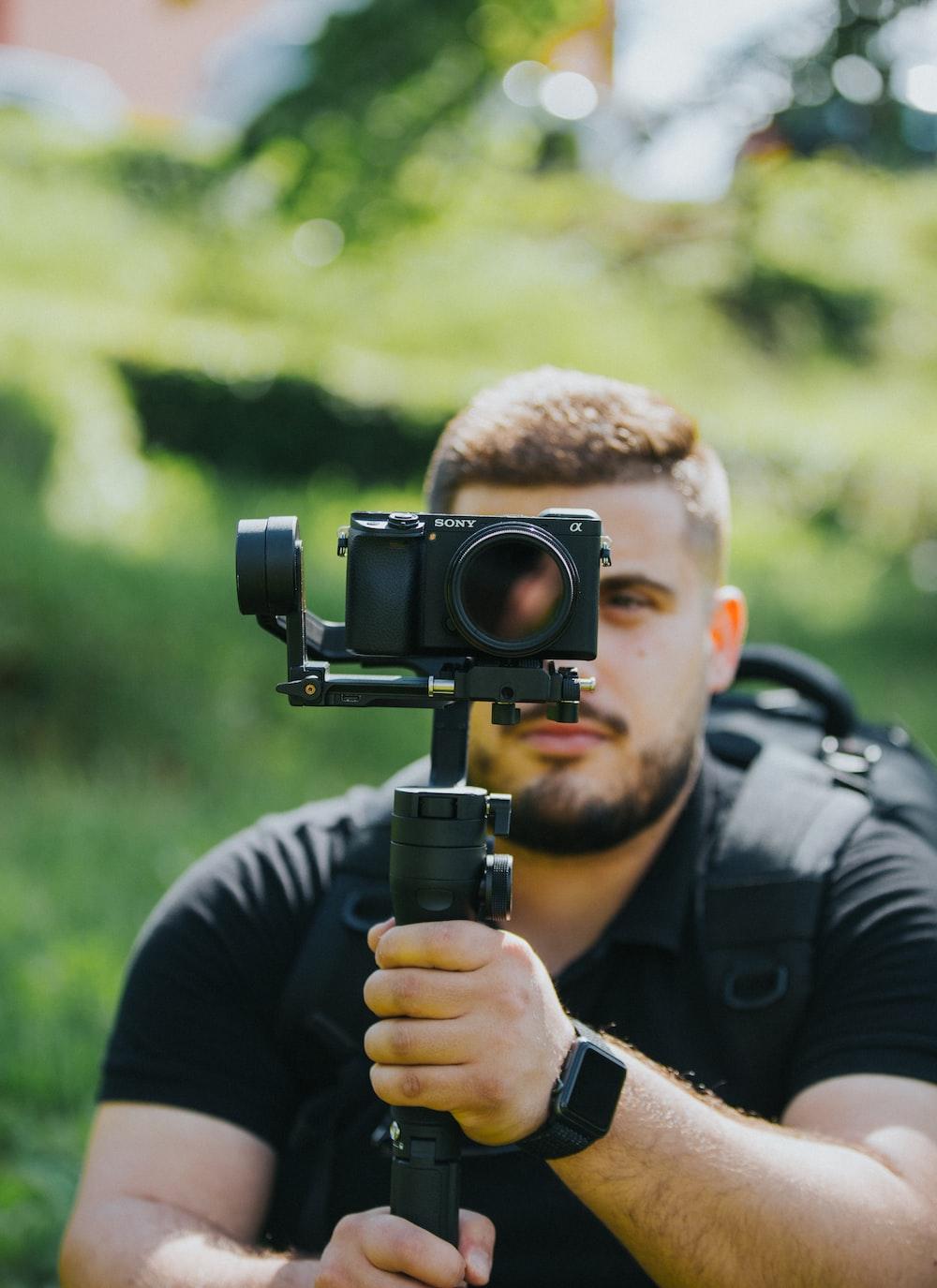 man wearing black shirt holding Sony DSLR camera