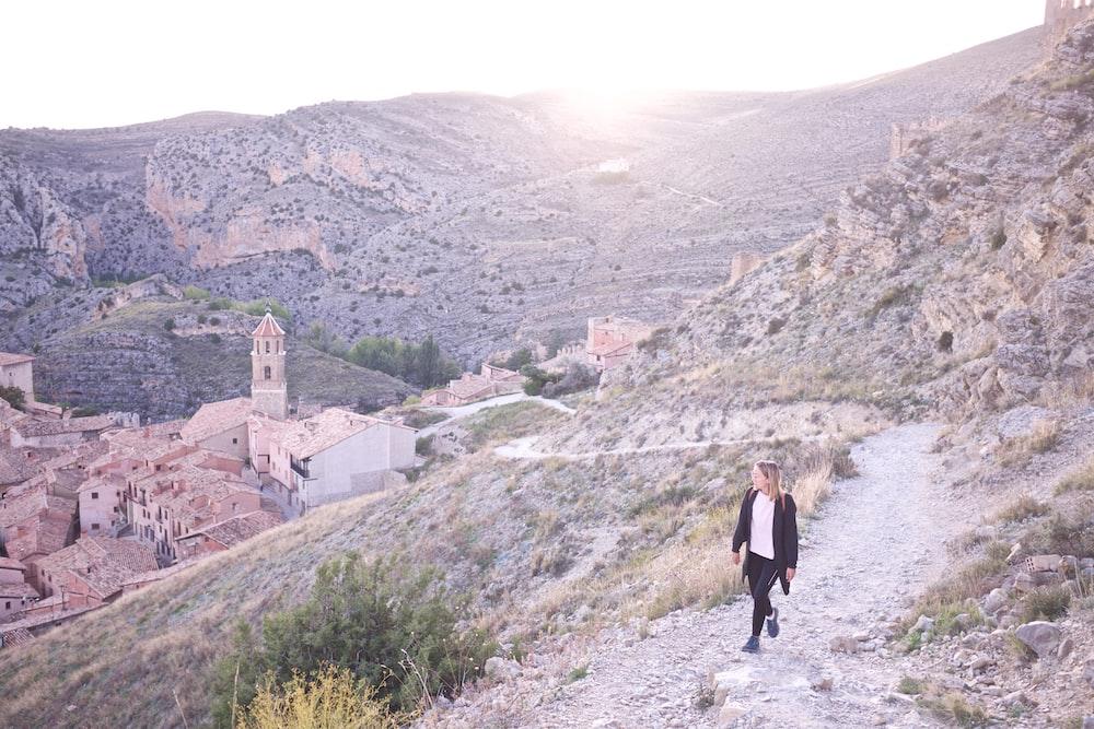 woman wearing black cardigan walking on the rocky field