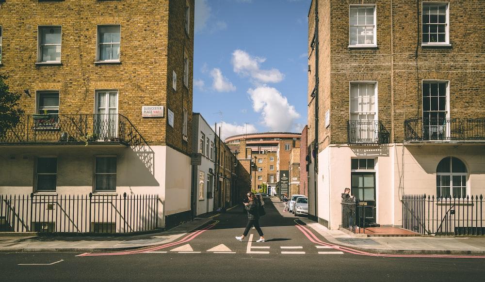person crossing on street between buildings