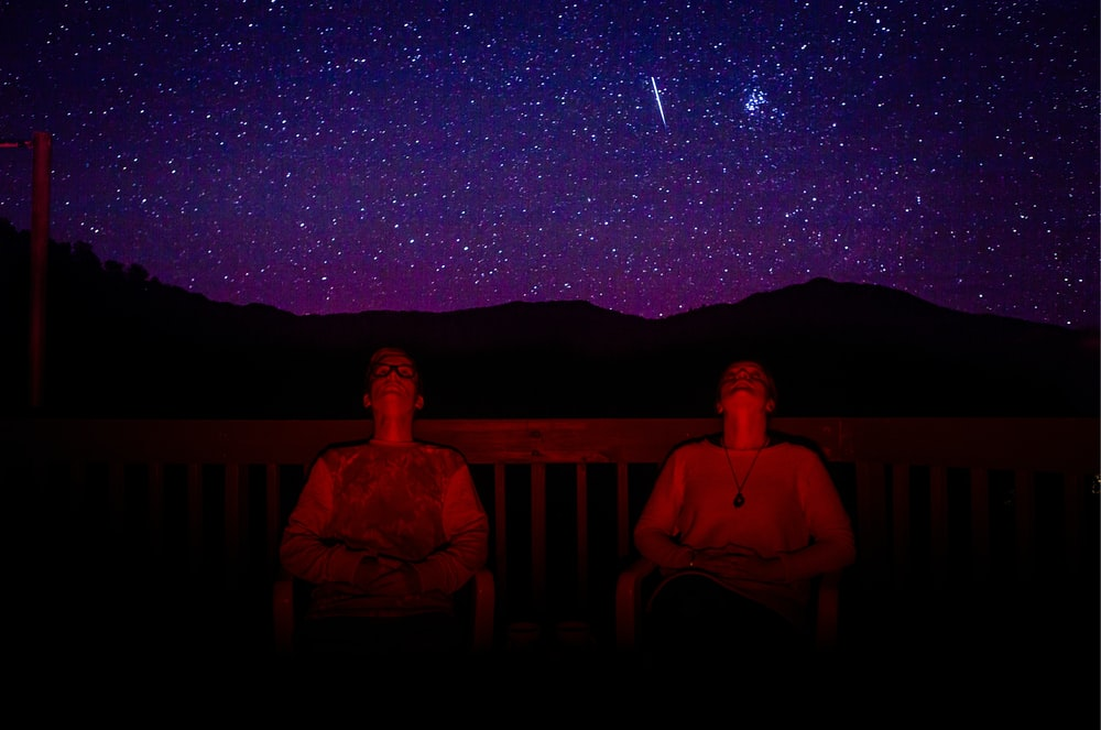 two men sitting under starry sky during nighttime