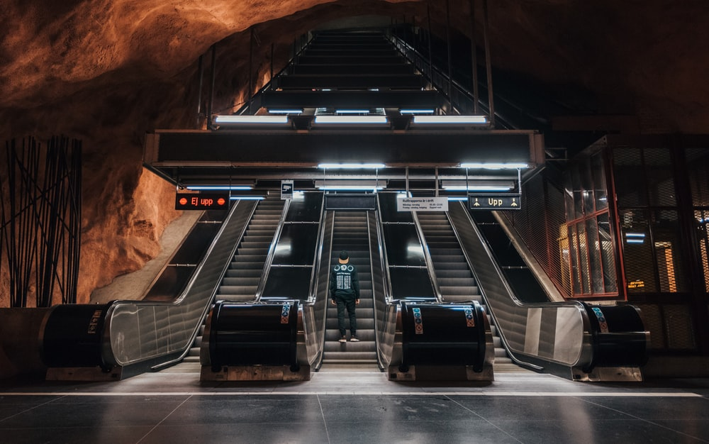 man with backpack going up escalator