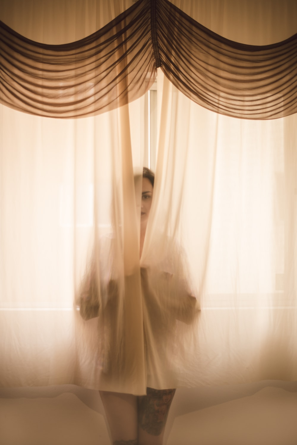woman hiding in window curtains