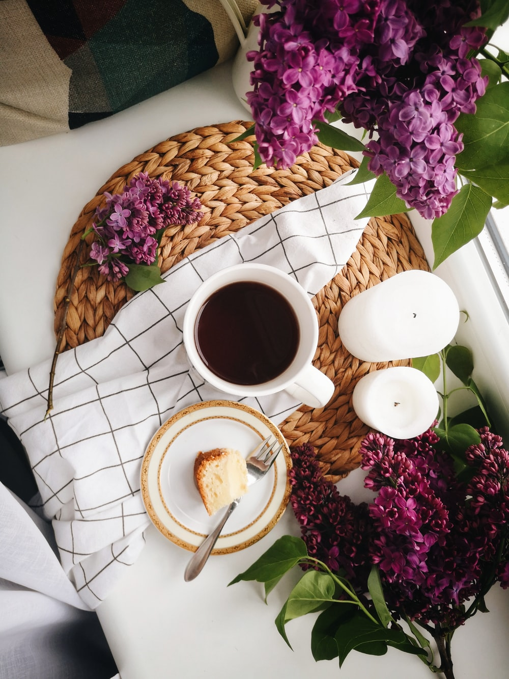 high angle photo of coffee in mug beside food and candles