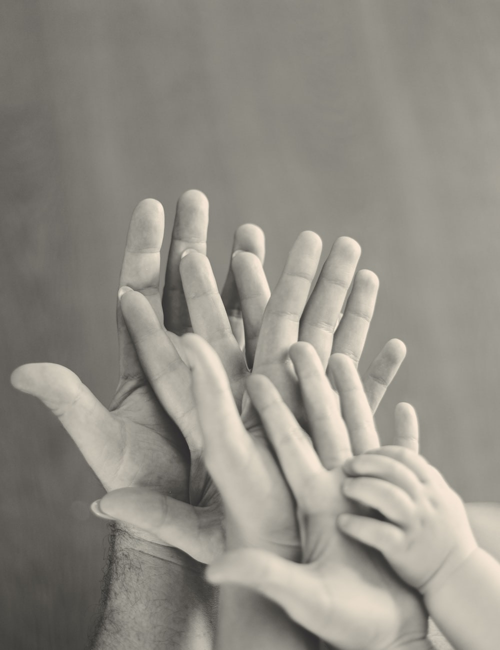 grayscale photo of family's hands