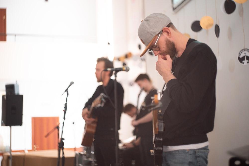 man wearing black crew-neck sweater playing guitar