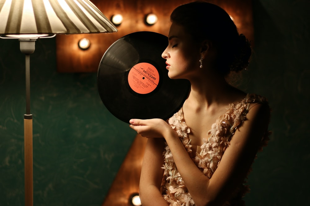 shallow focus photo of woman holding vinyl record