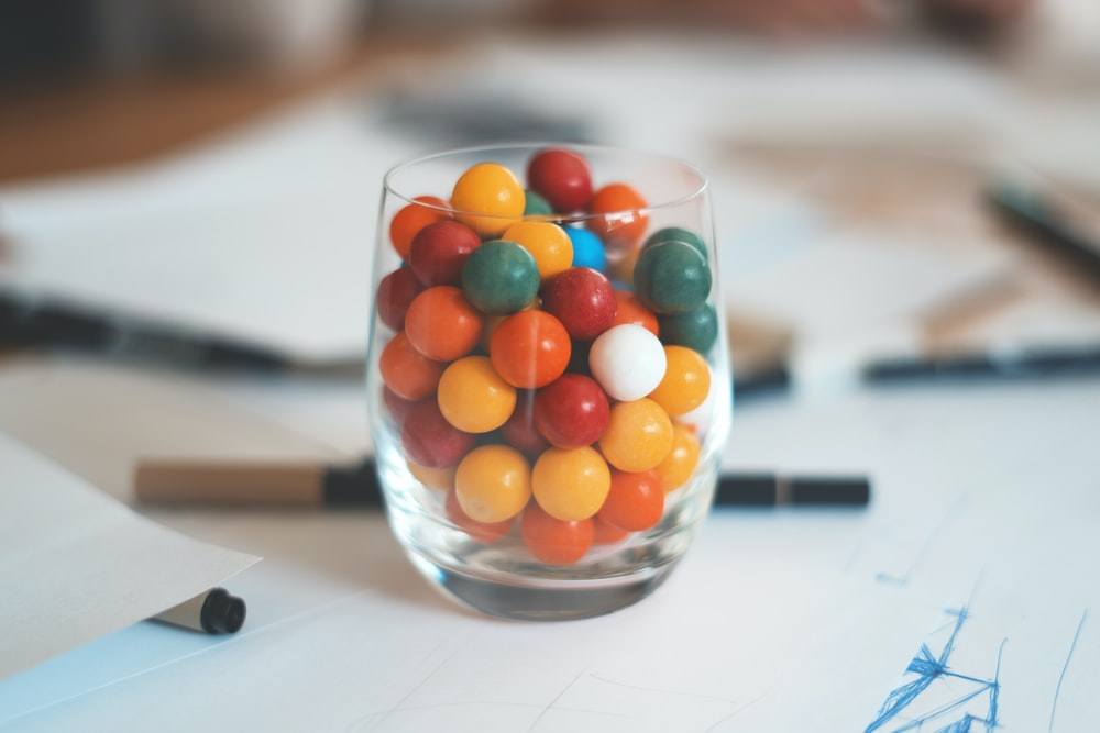 multicolored balls in clear shot glass