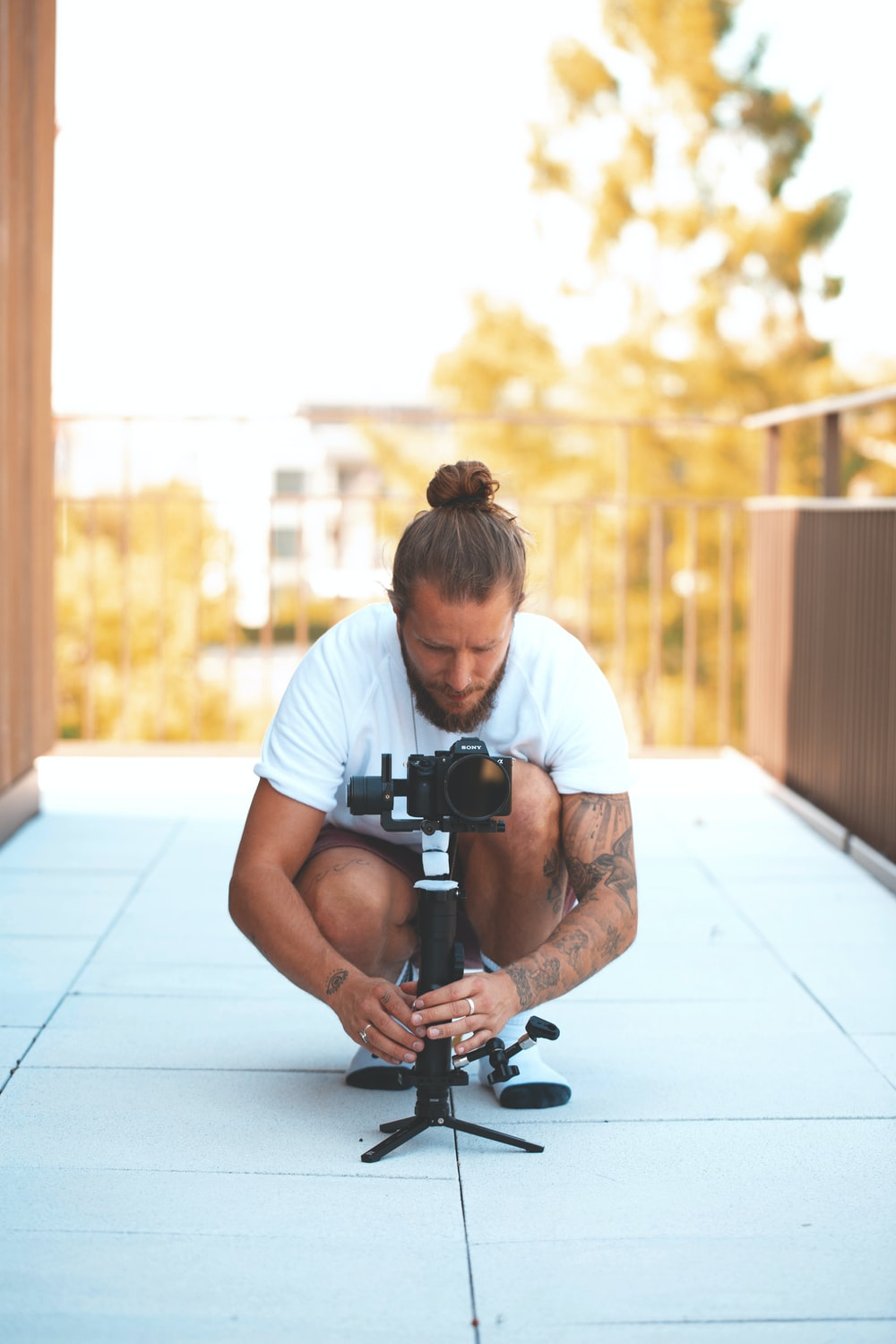 shallow focus photo of man in white T-shirt using DSLR camera