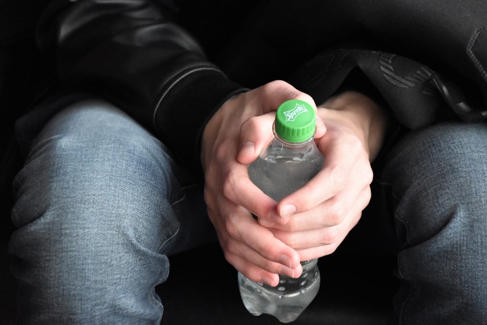 close-up photo of sitting person holding bottled water