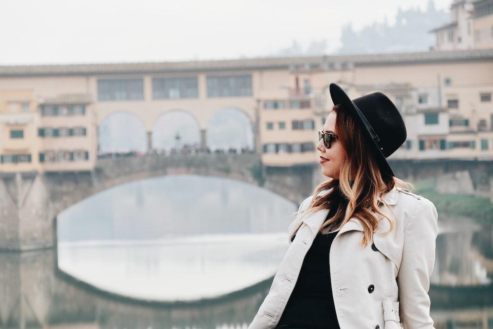 woman wearing gray jacket standing near bridge during daytime