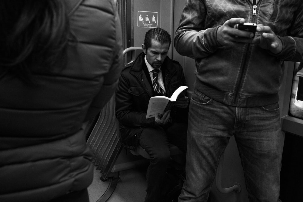 grayscale photo of man reading book