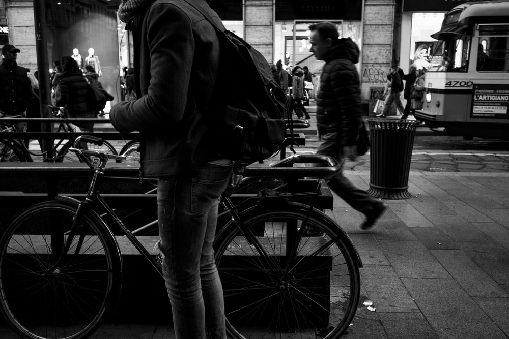 grayscale photography of person beside bicycle