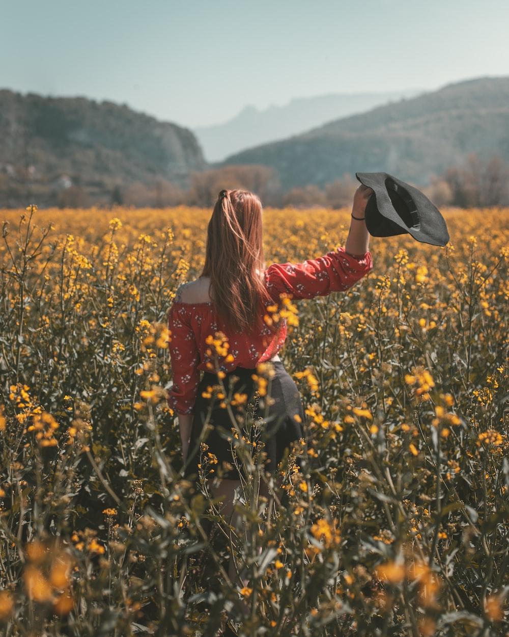 woman holding hat in flower field