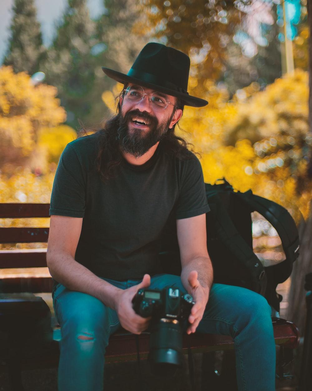 smiling man holding camera