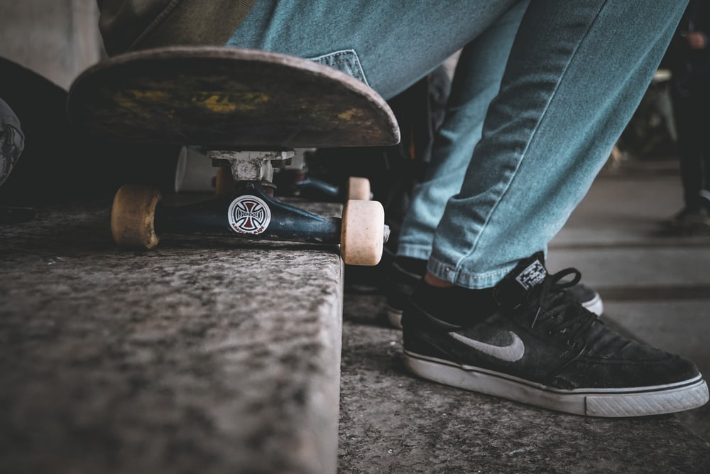 unknown person sitting on black skateboard outdoors