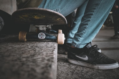 unknown person sitting on black skateboard outdoors footwear zoom background