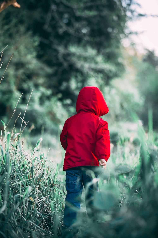 toddler walking on grass field during daytime