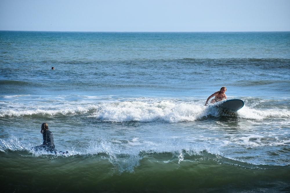 man on top of surfboard near sea shore