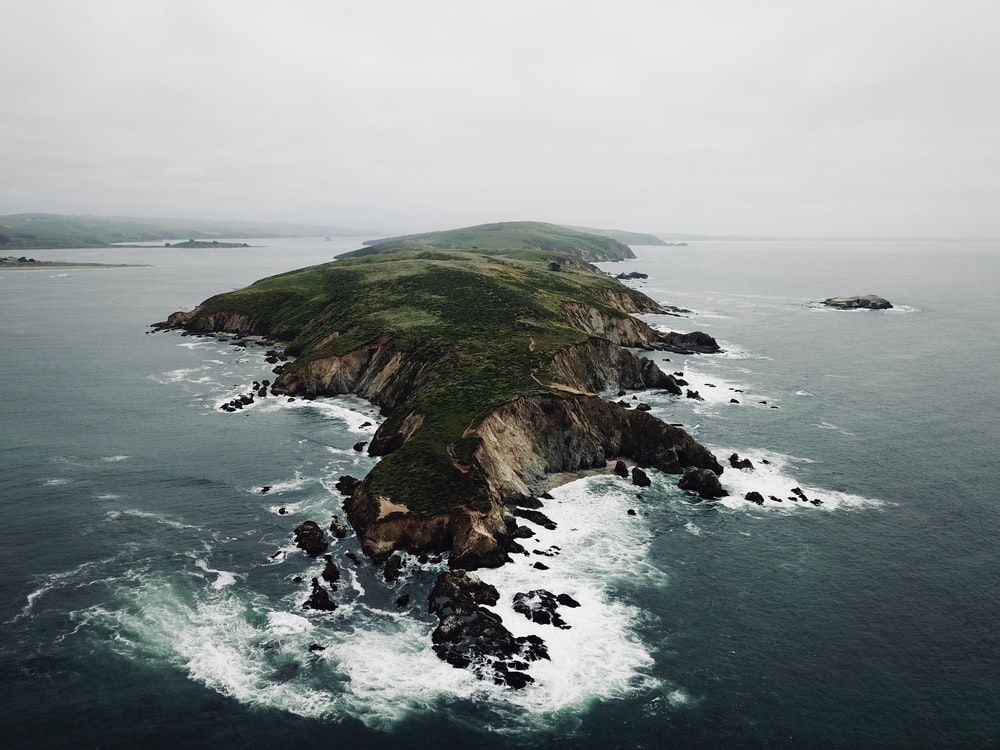 landscape photography of island surrounded with body of water