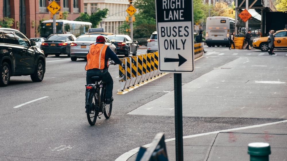 man riding bicycle on street near cars