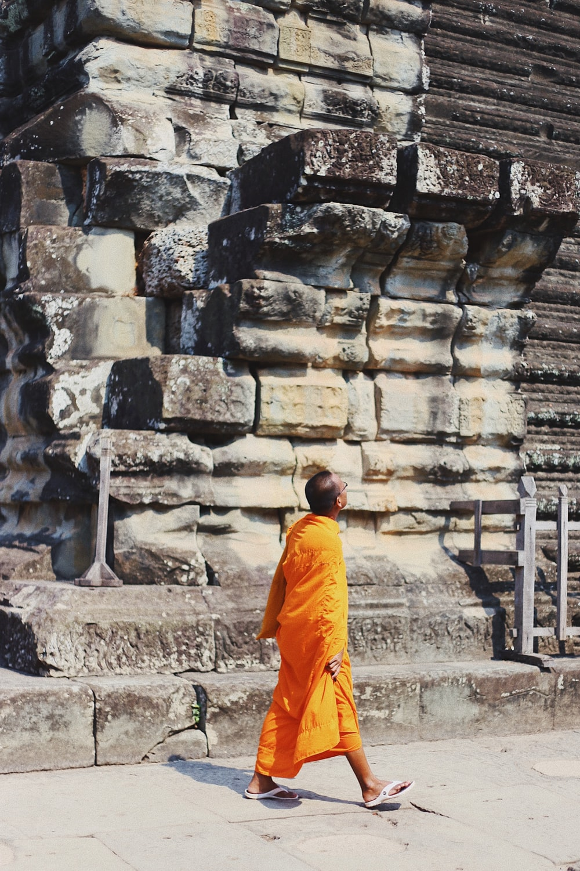 monk walking along sidewalk while looking up