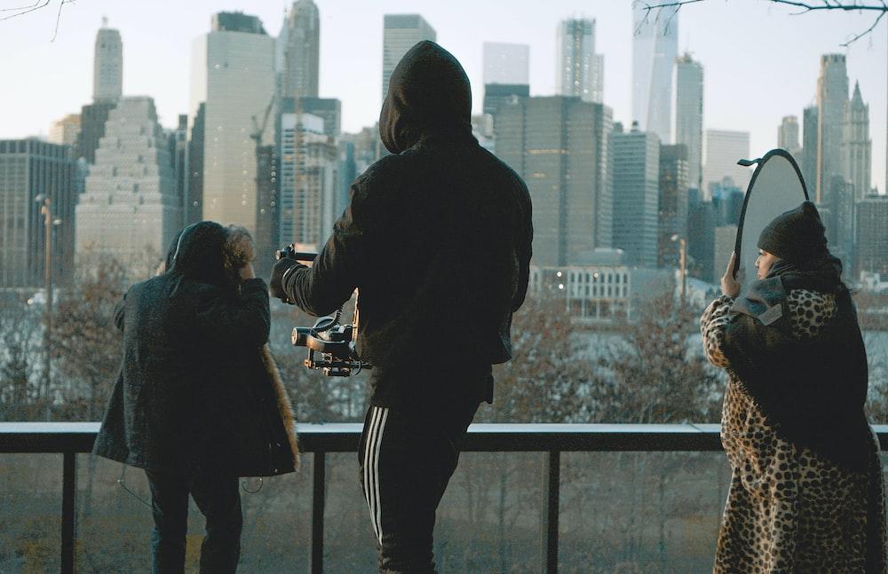 person wearing black hoodie standing beside metal railing during daytime
