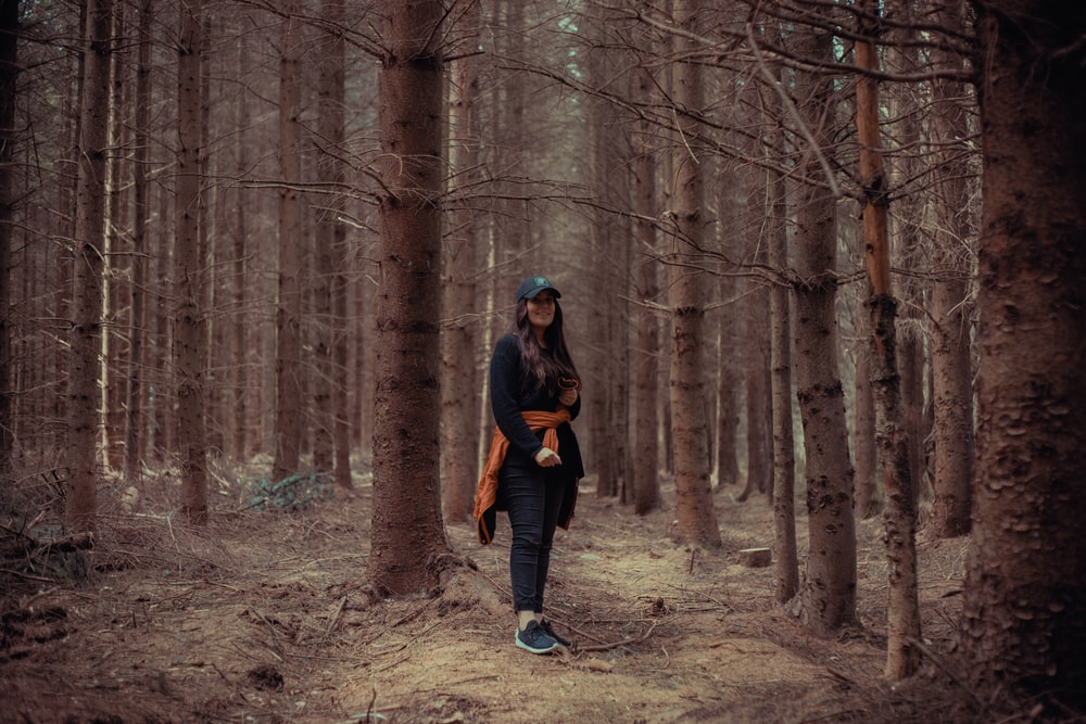 woman surrounded by bare trees