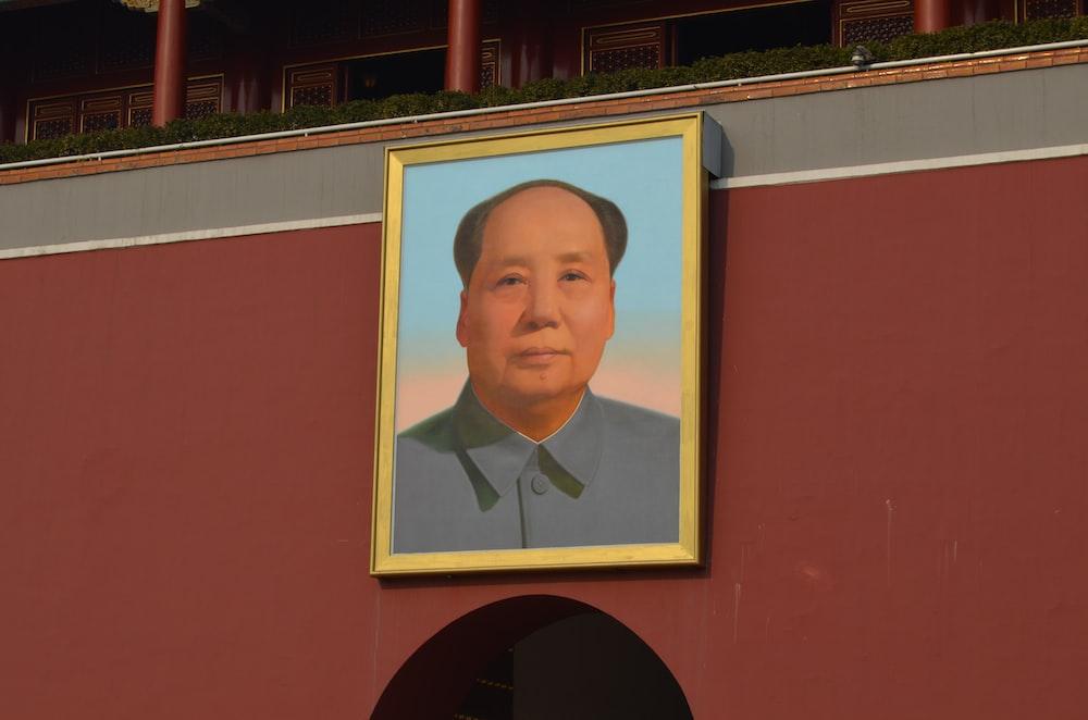 man wearing blue shirt photo on wall