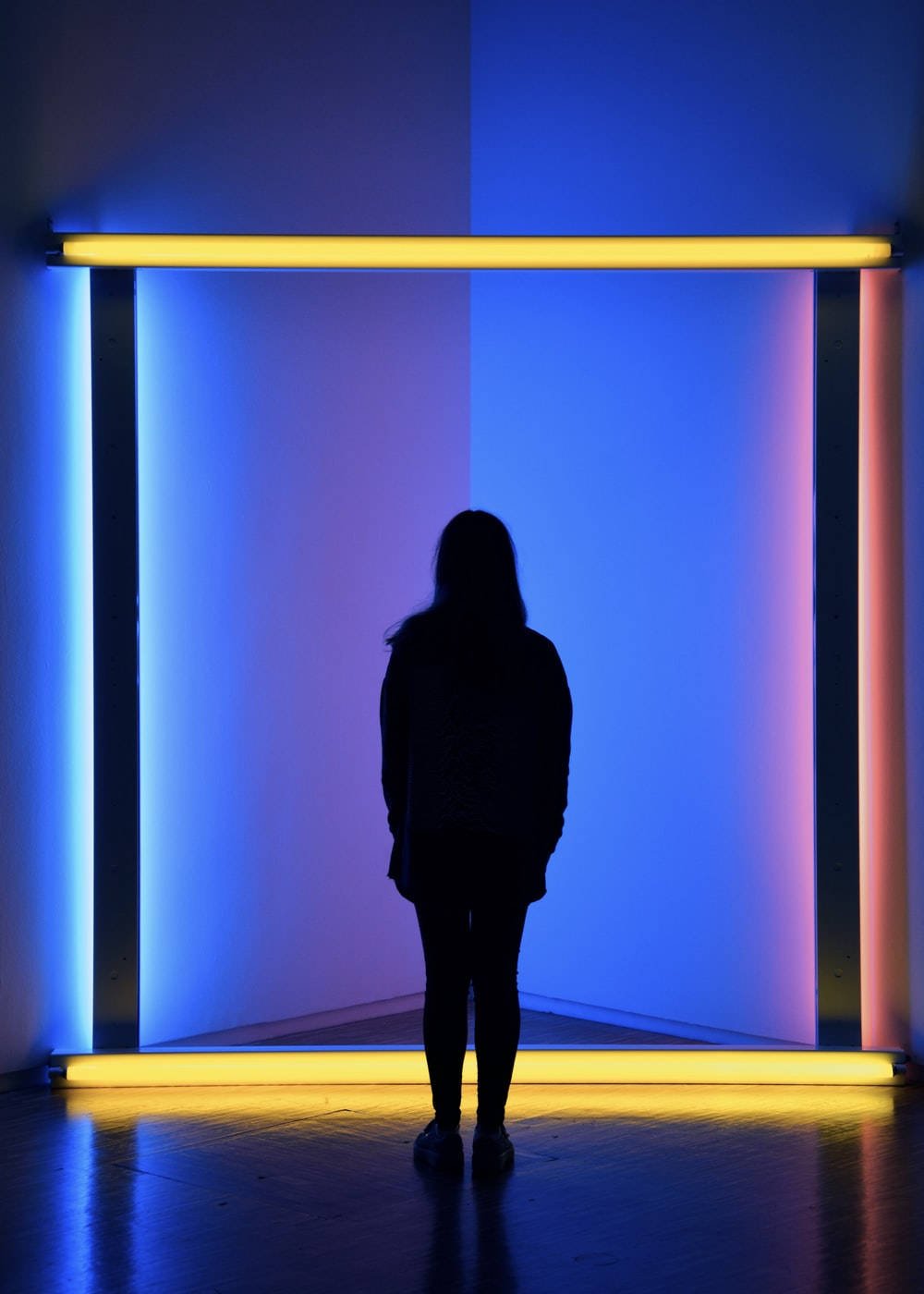 silhouette of woman standing beside yellow light bars