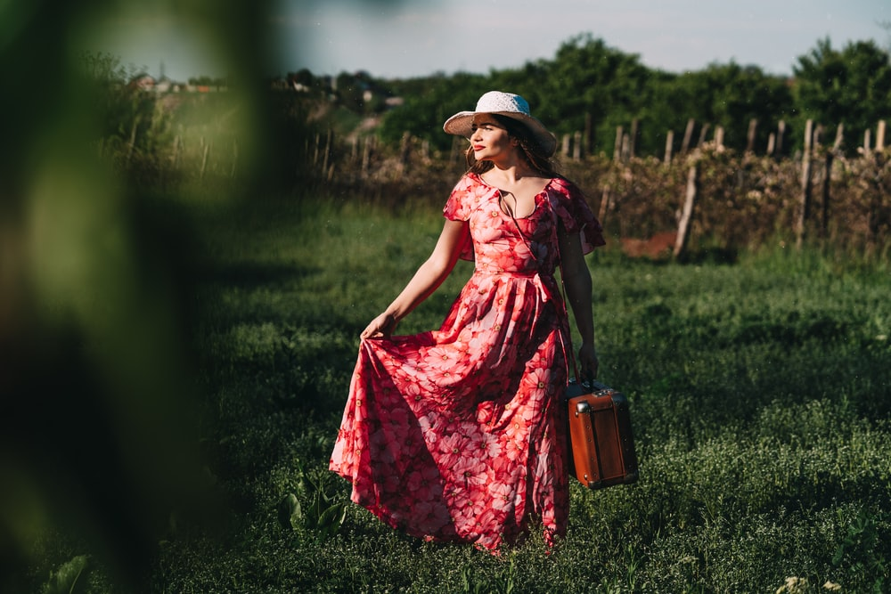 woman wearing red floral cap-sleeved maxi dress