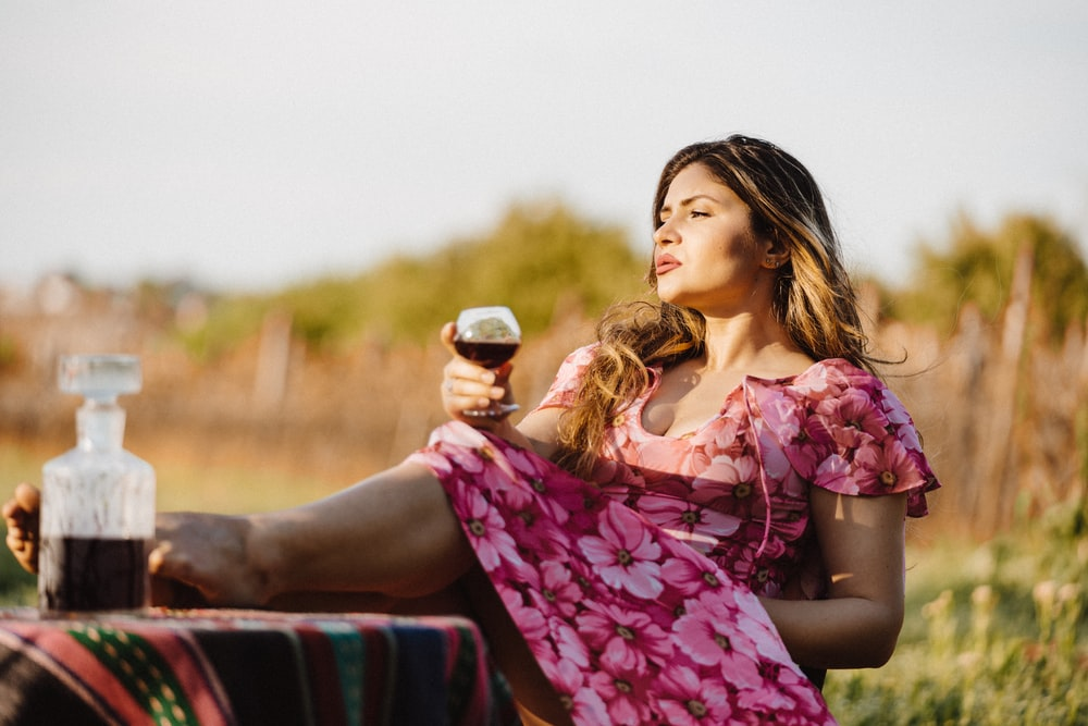 woman sitting in picnic table holding wine glass