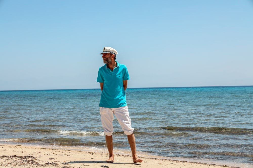 man wearing blue polo shirt and white shorts standing on seashore during daytime