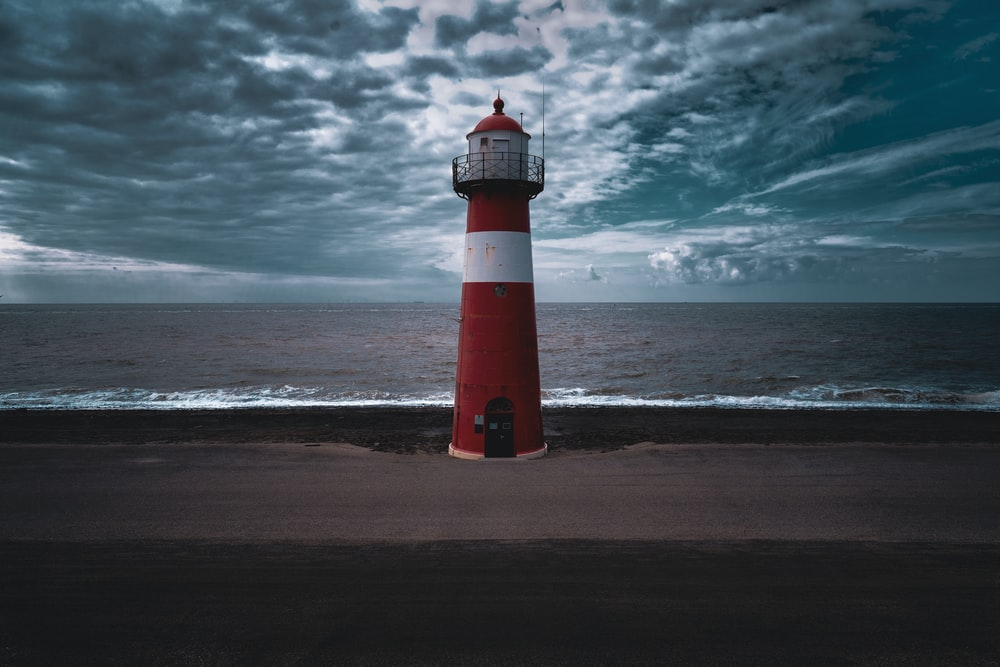 red and white lighthouse under gray clouds at dyatime