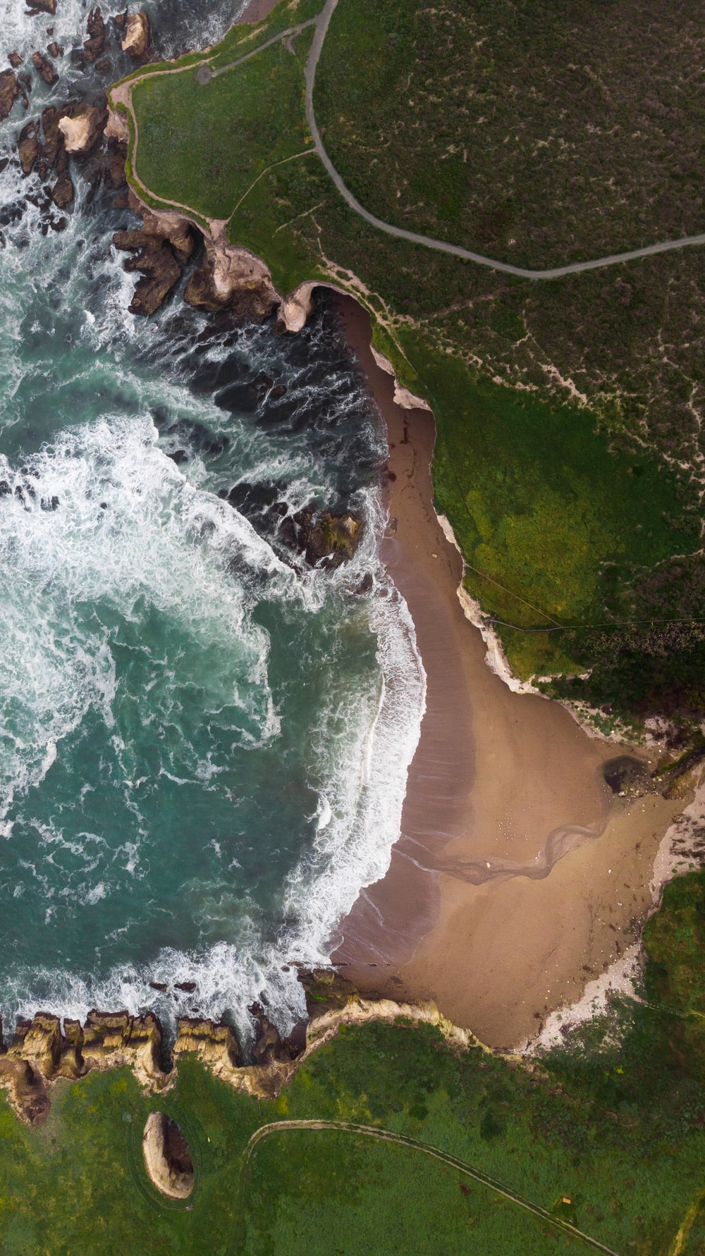 aerial view of ocean and green cliff