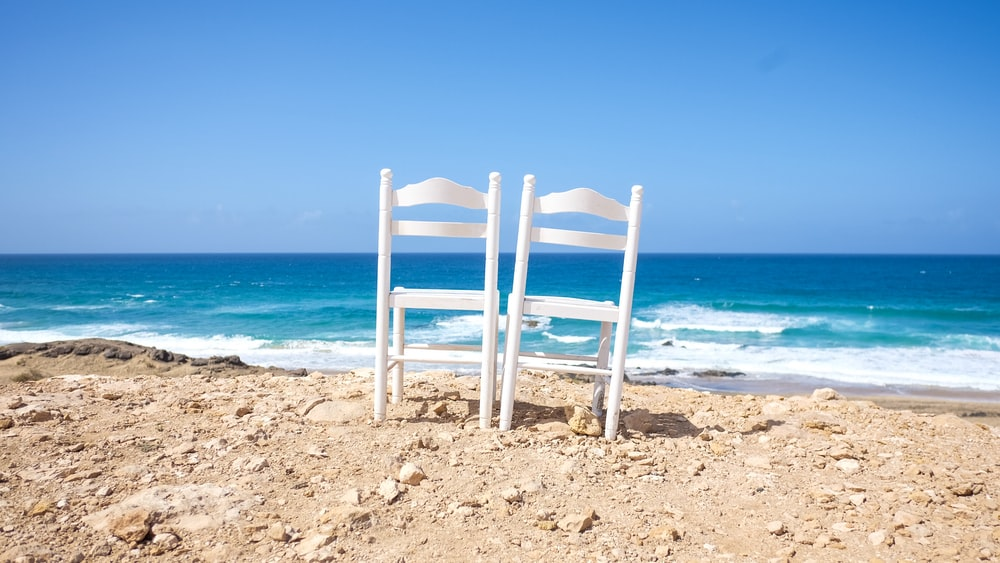 white wooden chairs on shore