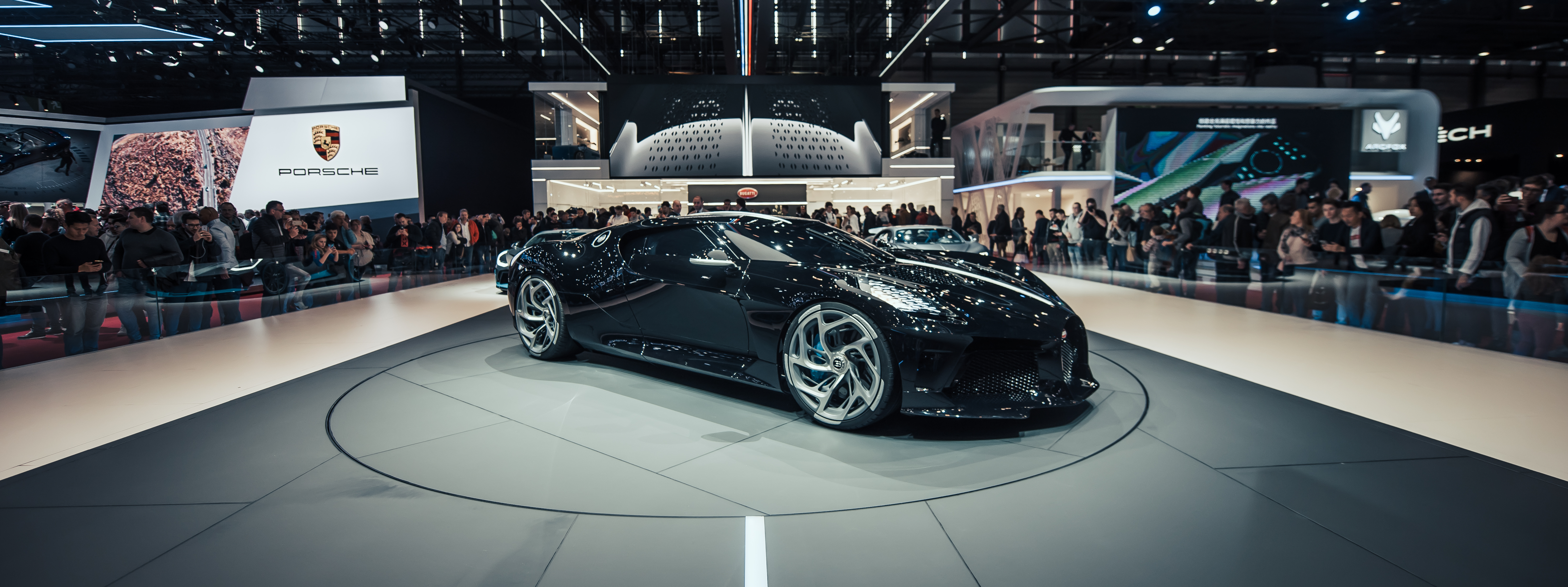 black Lamborghini on display surrounded with people watching