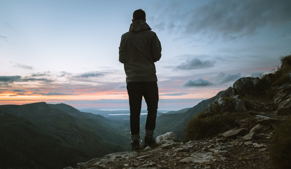 man in grey hoodie standing on cliff during sunrise