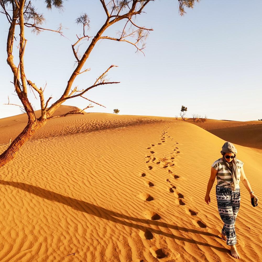 woman walking in brown sand dune leaving footprints in sand