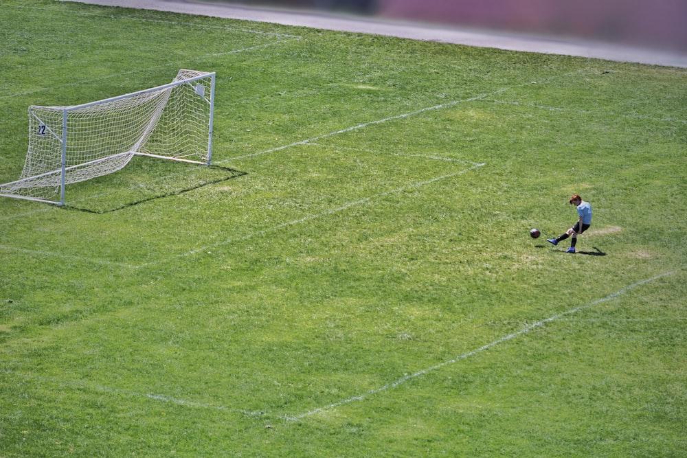 person kicking ball near white goalpost