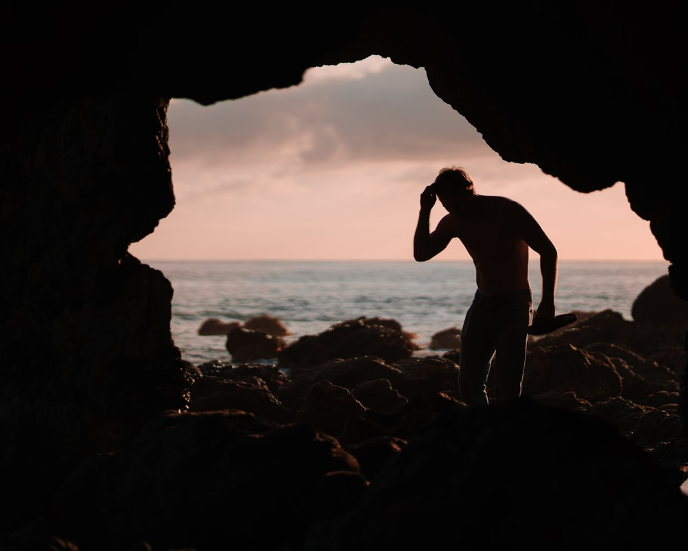 silhouette of man in cave