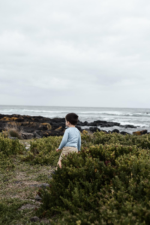 boy standing near ocean