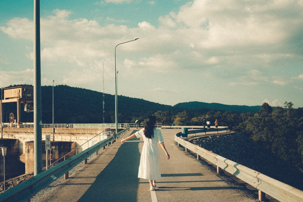 woman in white dress walking in road