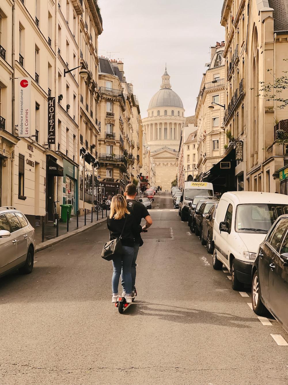 man and woman riding kick scooter