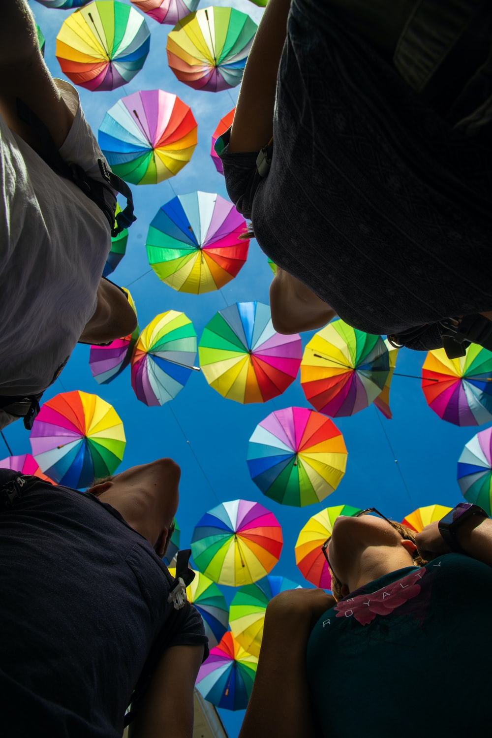 low-angle photo of people under colorful umbrellas